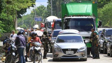 Soldiers search vehicles of fleeing residents at a checkpoint following the siege by Muslim militants in the outskirts of Marawi.
