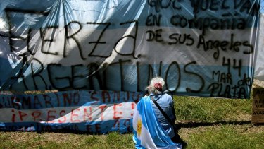 A woman sits in front of a banner blanketed with messages of support for the missing crew members of the ARA San Juan.