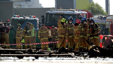 Firefighters at the scene of the plane crash at the Essendon DFO.