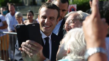 Emmanuel Macron poses for a selfie after voting in the final round of parliamentary elections. The new French president is riding a wave of popularity.