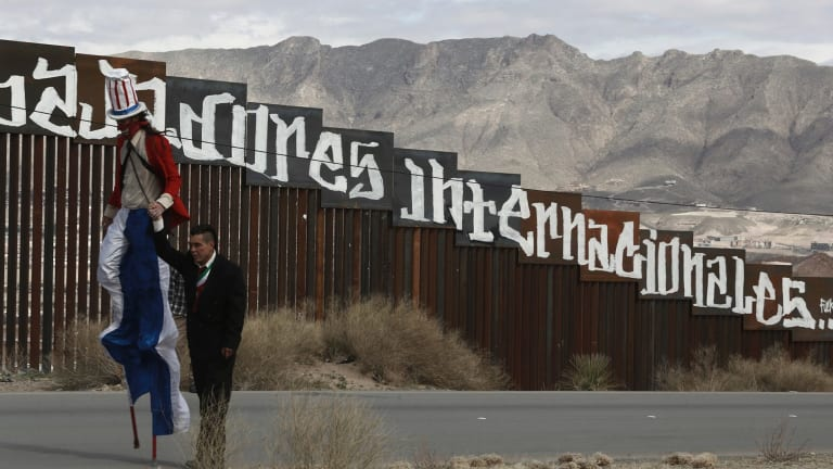 Protestors dressed as a diabolical Uncle Sam, on stilts, and Mexico's President Enrique Pena Nieto hold hands as they walk along the border fence in Ciudad Juarez.