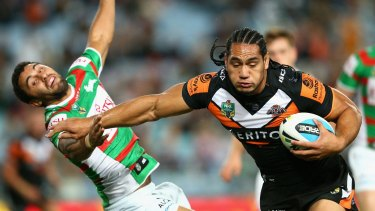 Hands off: Martin Taupau of the Tigers sends Souths fullback Alex Johnston flying.