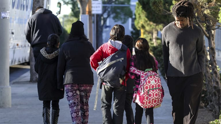 Parents take their children back home on Tuesday after the threat closed schools across Los Angeles.