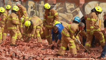 Firemen and workers frantically dig in the rubble of the fallen wall in March 2013. Three people died when the structure fell on them.