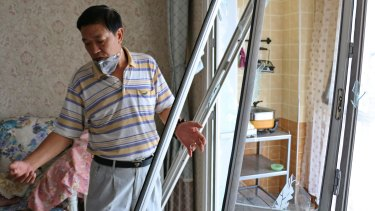 Wang Jiaming surveys the damage in his apartment, over a kilometre from the blast site in Tianjin.