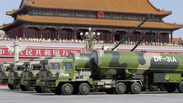 A parade of military power in Beijing in September.  Military vehicles carrying DF-31A long-range missiles drive past the Tiananmen Gate.