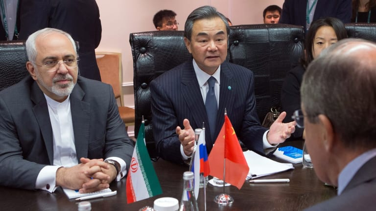 Iranian Foreign Minister Mohammad Javad Zarif (left) and Chinese Foreign Minister Wang Yi (centre) meeting with their Russian counterpart Sergei Lavrov.