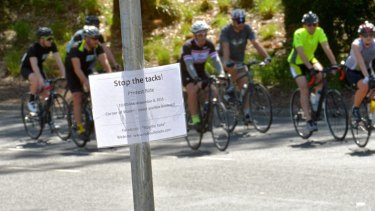 About 400 riders have protested against tacks being left on a popular cycle track.