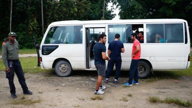 Asylum seekers return to the bus after a visit into town on Manus Island in April.