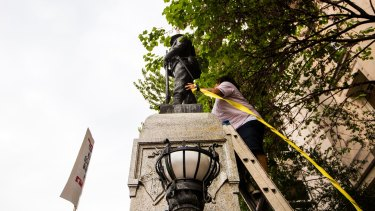An unidentified protester climbs a ladder to place a rope around a Confederate statue during a rally on Monday.