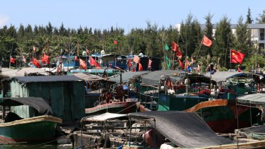 Fishing vessels moored at Tanmen wharf fly the flag of the People's Republic.