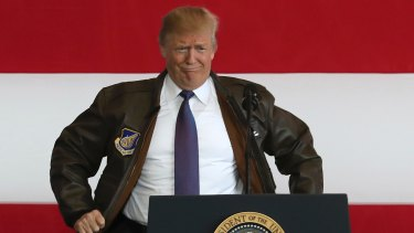 President Donald Trump puts on a military jacket as he meets the US troops at the U.S. Yokota Air Base, on the outskirts of Tokyo on Sunday