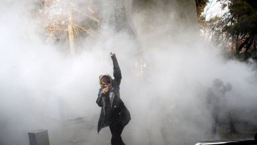 In this photo obtained but not taken by the Associated Press, a university student attends a protest last week inside Tehran University while a smoke grenade is thrown by anti-riot Iranian police.