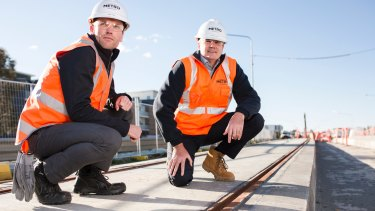 The test track slabs for the light rail have been laid. From left, Mark Jones deputy project director, and Glenn Stockton Canberra Metro CEO, next to the epoxy compound that encases the rail to both secure the rail in the track slot and as part of the stray current management system.