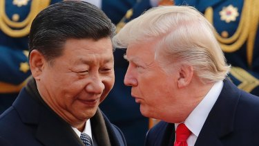 President Donald Trump, right, chats with Chinese President Xi Jinping during a welcome ceremony at the Great Hall of the People in Beijing on November 9.