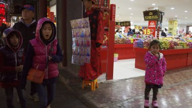 Children pass by a man dressed like an emperor, centre, promoting photography services in Beijing.