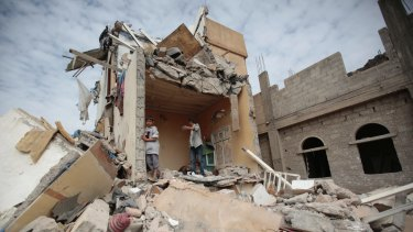 Boys stand on the remains of a house destroyed by Saudi-led airstrikes in Yemen in August.