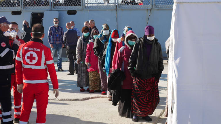 Safe landing: Refugees rescued by a Spanish navy vessel involved in Operation Triton line up in Sicily.