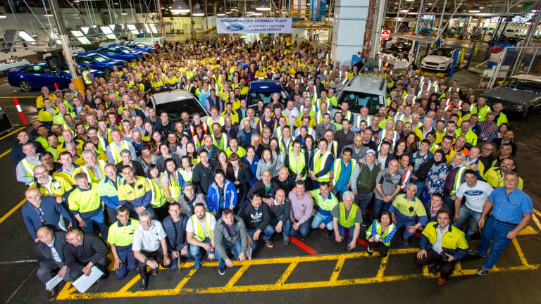 Job done: Ford employees gather around the Falcon XR6 after it rolled off the assembly line in Melbourne.