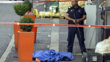 An Israeli policeman stands by the body of a Palestinian at the scene of a stabbing attack in Jerusalem.