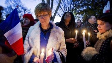 Alexandra Salomon, from Paris, France, centre, joins a vigil outside the White House in Washington DC.