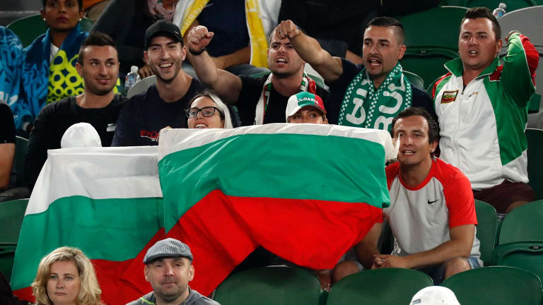 Supporters of Dimitrov cheer him.