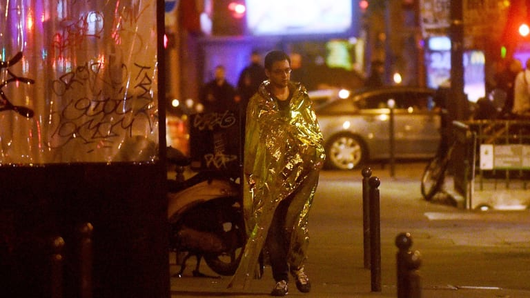 A survivor walks in the street after gunfire in the Bataclan concert hall in Paris, France.