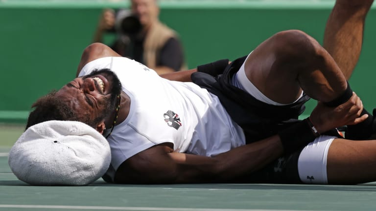 German Dustin Brown grabs his ankle after falling.