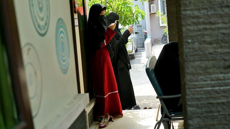Niqab Squad members check their phones outside a gathering in Bogor, Indonesia.