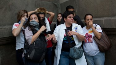 People protect themselves from tear gas in Rio de Janeiro, on Friday.