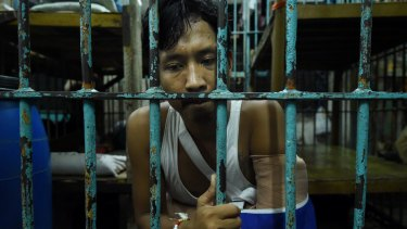 Wounded drug user Francisco Maneja, 27, sits in a cell at Manila Police Headquarters.