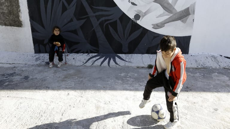 Children play at the Hellenikon shelter, a former Olympic  hockey venue, in southern Athens. A tightening of border controls closer to the promised lands of Germany and Sweden has left thousands trapped and destitute in Greece.