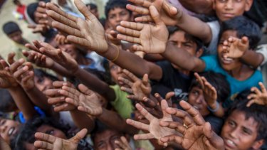 Rohingya Muslim children, who crossed over from Myanmar into Bangladesh, stretch their arms out to collect chocolates and milk distributed by Bangladeshi men.