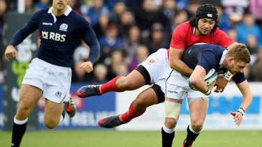 Finn Russell of Scotland is tackled by Latiume Fosita of Tonga.