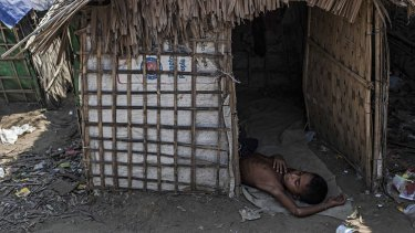 A Rohingya boy naps in his family's temporary shelter next to an internal displacement camp in Myanmar.
