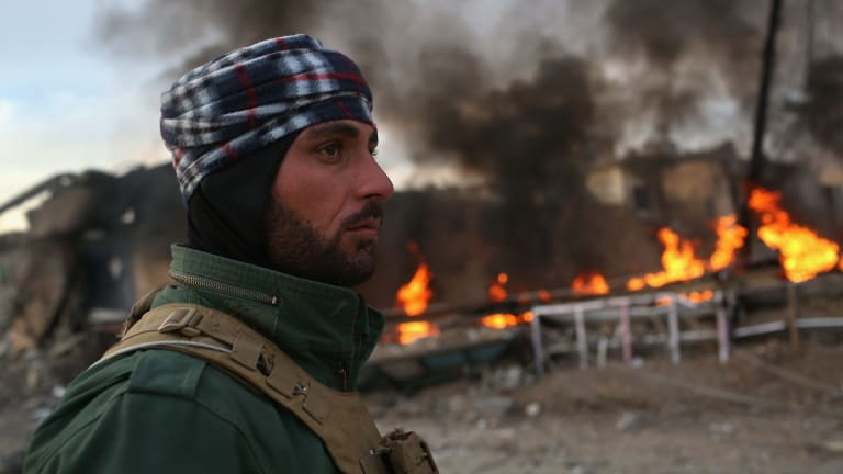 A Kurdish soldier passes by tyres set on fire by Islamic State militants to hinder airstrikes in Sinjar, Iraq.