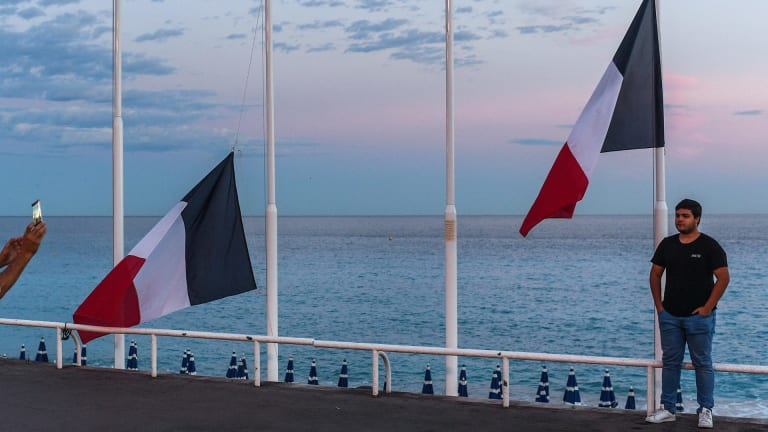 A man poses for a picture next to French flags flying at half mast on the Promenade des Anglais in Nice, France.