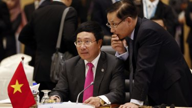 Vietnam's Foreign Minister Pham Binh Minh, left, listens to his delegation member during the Association of Southeast Asian Nations foreign ministers meeting plenary session in Kuala Lumpur.