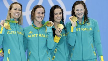 Bronte Campbell, second left, and Cate Campbell, right, show off the gold medals they won on the first night in Rio.