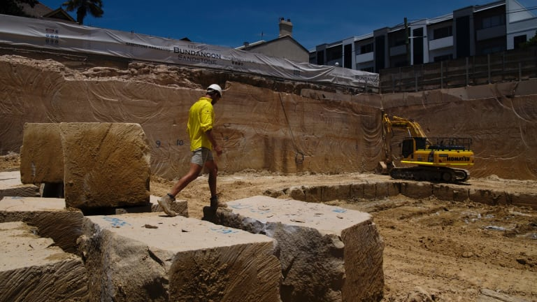 A worker traverses the yellow block boulders at the Bundanoon Sandstone quarry in Harris Street, Pyrmont.