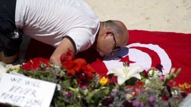 A man kisses a Tunisian flag at the site of a shooting attack on the beach in front of the Riu Imperial Marhaba Hotel in Port el Kantaoui.