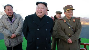 Kim Jong-un, centre, smiles during a missile launch in March.