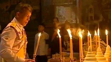 Thailand's new King Maha Vajiralongkorn Bodindradebayavarangkun lights candles for his father at the Grand Palace in December.