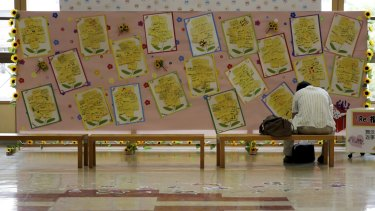 A tourist sits near messages of support for survivors, at Fukushima station in Japan last month.