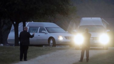Two hearses arrive with the caskets of Richard and Therese Rodriguez at the Sutherland Springs Cemetery, on Saturday.