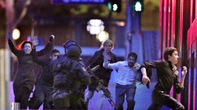 Hostages flee from Sydney's Lindt Chocolate Cafe in December.