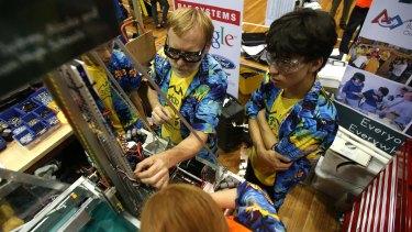 Robots kicking goals: Thunder's pit crew make repairs after a match.
