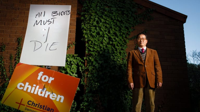 Rev. David Kim with an ACT Christian Democratic Party's anti-safe schools campaign sign which had been torn in half and defaced with an intimidating threat.