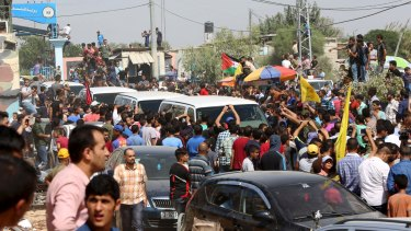 Residents gather around the vehicles to welcome PM Rami Hamdallah, who is in Gaza for the latest attempt at reconciliation.