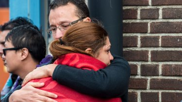 People comfort each other after being evacuated from Brussels airport, after the explosions.